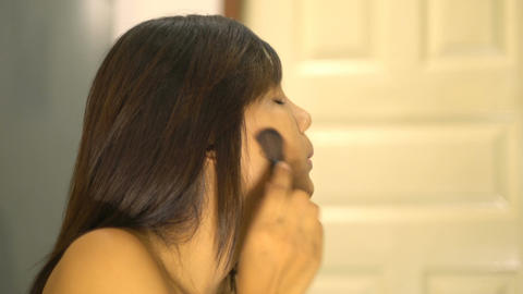 Young Asian Woman applying powder with big brush Footage