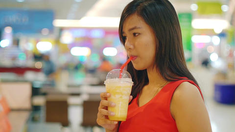 Young Asian Lady drinking orange juice in food court Footage