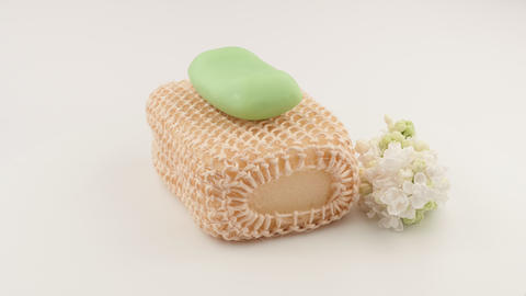 Soap on the washcloth and branch of white lilac. White background Live Action