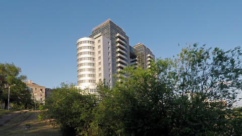 cityscape, building against the sky with trees and a pond in the foreground Live Action