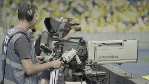 Cameraman with a camera in the stadium during a football match. TV Live Action