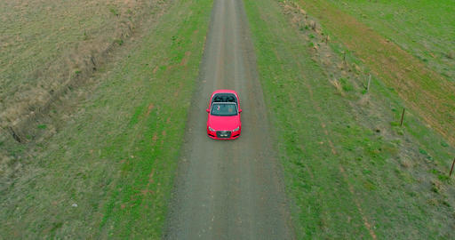 Aerial view of a red car driving on country road Live Action