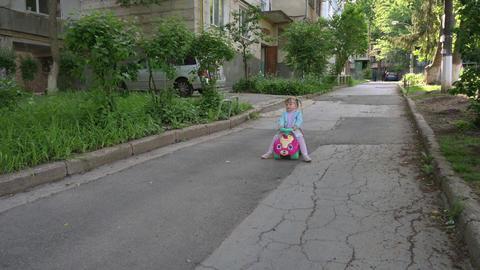 Child riding a toy car in the park Acción en vivo