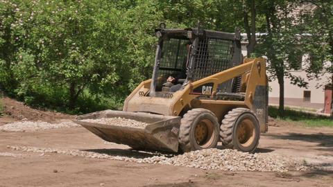 Skid steer loader moving sand soil at construction area outdoors Acción en vivo