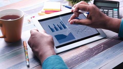 Man hand analyzing chart on digital tablet at office desk Acción en vivo
