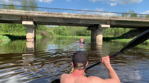 Russia, Gatchina, 29 May 2020: The young men in a cap floats on a kayak under Acción en vivo