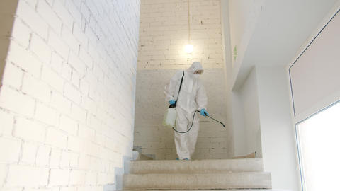 Biohazard specialist disinfecting building using liquid chemicals working alone Live Action