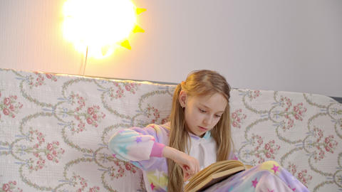 Teenager girl in pajamas reading book in bedroom with night light lantern Live Action