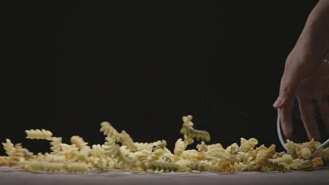 Girl's hands are pouring fresh homemade raw Rotini from glass bowl on a brown Live Action