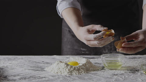 Step by step homemade dough preparation. Woman's hands separete the second yolk Live Action