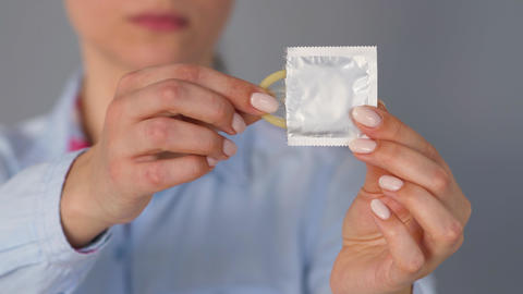 Female hands demonstrating condom before camera, safe sex, contraception Live Action