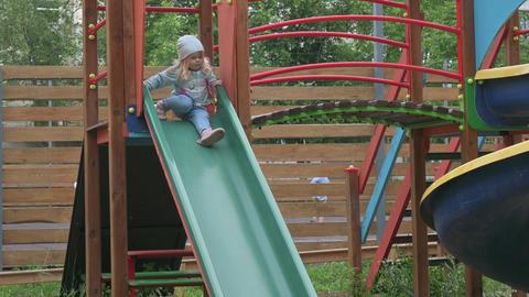 Cute blond preschool girl sliding the childrens slide Live Action