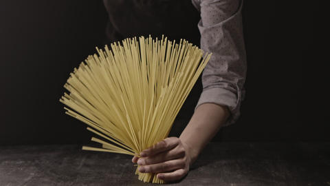 The bunch of raw spaghetti in female hands on black wood vintage table on a Live Action