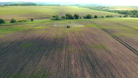 Aerial view Farm machinery spraying insecticide to the green field, agricultural Live Action