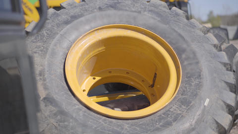 Close-up of large tractor wheel lying outdoors. Big part of industrial machinery Live Action