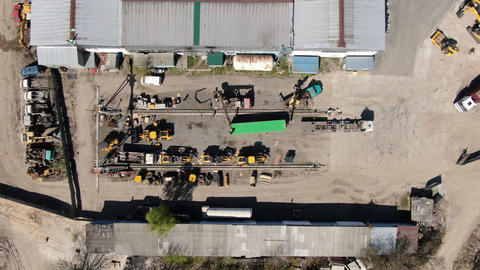 Aerial view of worker fastening ropes on large green shipping container. Drone Live Action