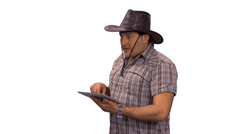A man in a cowboy hat using a tablet computer, alpha channel Footage