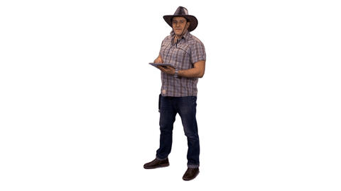 A man in a cowboy hat standing and looking at tablet computer, alpha channel Footage