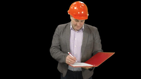 An industry businessman technical manager in helmet is standing & takes notes Footage
