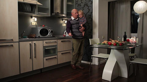 Grandfather holding boy and setting festive table Footage