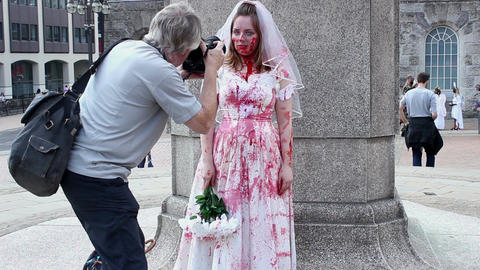 Bloodied zombie bride posing for pictures in public square ビデオ