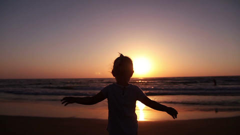 Little girl waving the setting sun on the beach Footage