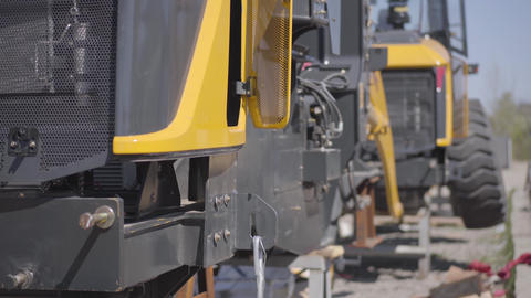 Close-up of heavy engineering machinery standing outdoors on sunny day. Yellow Live Action