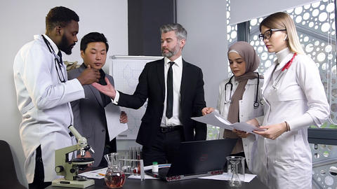 Multi ethnic team of successful doctors finishing clinical trials on computer Live Action