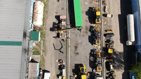 Drone moving along construction site with heavy machinery and shipping Live Action