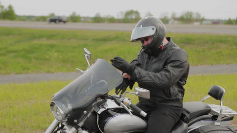 Man biker on a motorcycle puts on equipment Live Action
