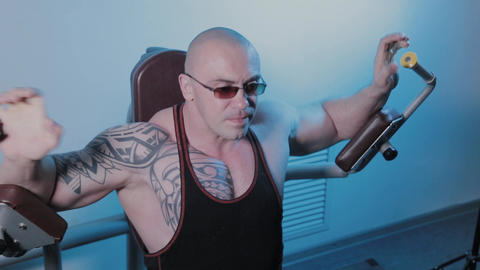 Professional bodybuilder trains pectoral muscles on the simulator in a sports GIF