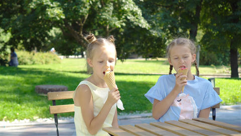 Little girls eating ice-cream outdoors at summer in outdoor cafe Live Action