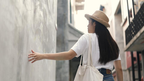 Beautiful Asian woman wears a vintage hat and holding a Cloth bag and use hands touching softly wall Live Action