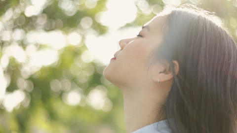 Close up portrait of young Asian woman relaxed enjoying peaceful sunset and looking up exhaling Live Action