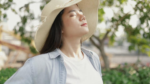 Beautiful asian woman wears a vintage hat relaxed enjoying peaceful sunset and looking up exhaling Live Action