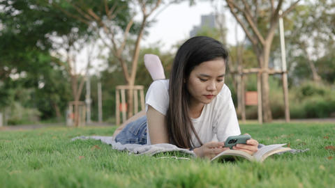 Attractive beautiful young asian woman relaxed reading a book and using smartphone while lying on Live Action