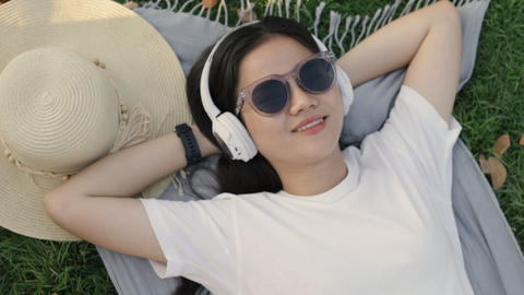 Beautiful young Asian woman wears sunglasses and headphones sleeping on the grass at home feeling Live Action
