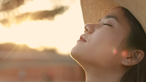 Close up portrait of beautiful Asian woman enjoying peaceful sunset and looking up exhaling fresh Live Action