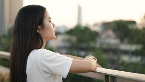 Asian woman enjoying peaceful sunset and exhaling fresh air relaxing outdoors Live Action
