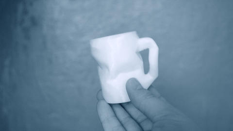 The person holds on his hands and view white object created on 3d printe Live Action