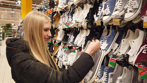 Woman holding a pair of nice sneakers for daily usage. Woman is shopping for new Live Action
