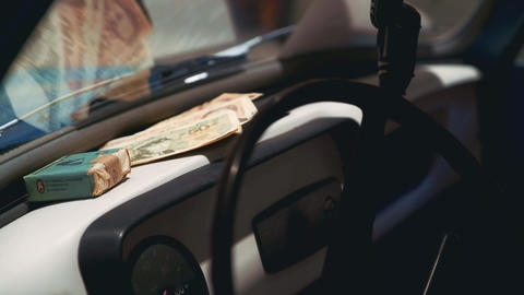 Old money and tobacco product on retro car dashboard Live Action