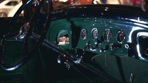 View of green antique car dashboard panel and steering wheel Live Action