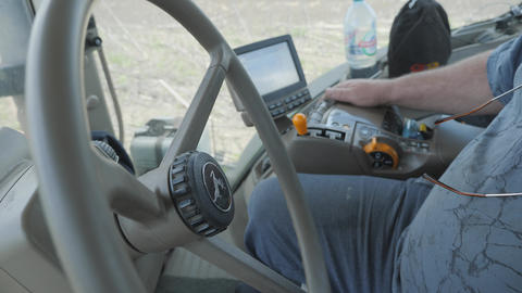 Operator's cab of a modern tractor with trailer equipment in the process of tillage before sowing, Live Action