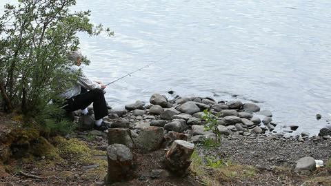 man fishing from rock shore P HD 0146 Footage