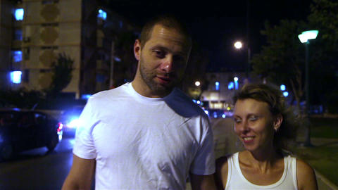 Man and woman walking on the street in the evening and talk Footage