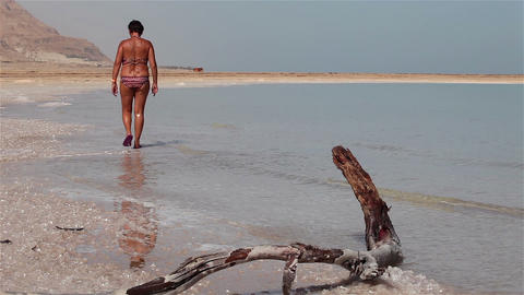 Woman walks along the shore of the Dead Sea Footage