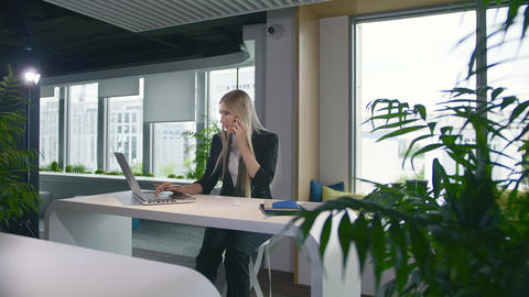 Trendy business woman watching laptop and speaking on phone. Stylish young blond Live Action