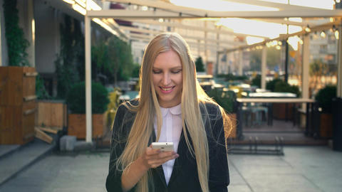 Formal business woman walking on street. Elegant blond young woman in suit and Live Action
