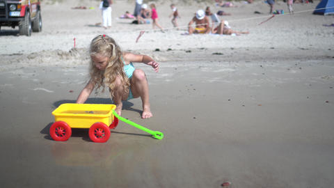 Lovely girl with curly blond hair digging sand to toy cart wagon on ocean shore Live Action